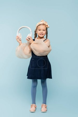 Photo for Full length of cheerful kid in headband with bow holding wireless headphones on blue - Royalty Free Image