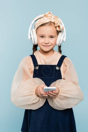 cheerful kid in headband with bow and wireless headphones holding smartphone isolated on blue
