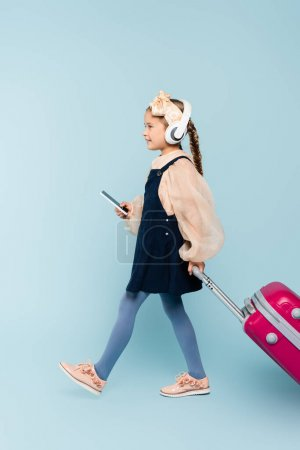 Photo for Full length of little girl in wireless headphones holding smartphone while walking with baggage on blue - Royalty Free Image