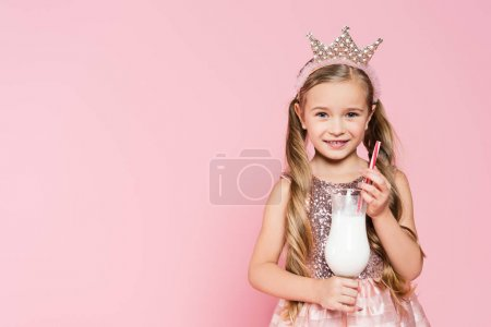 Photo for Happy little girl in dress and crown holding glass with milkshake isolated on pink - Royalty Free Image