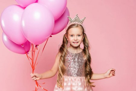 Photo for Cheerful little girl in dress and crown holding balloons isolated on pink - Royalty Free Image