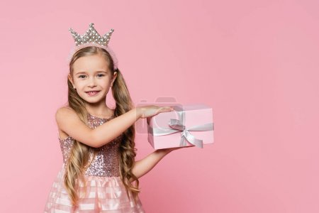 Photo for Joyful little girl in crown holding wrapped present isolated on pink - Royalty Free Image