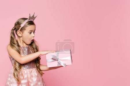 Photo for Surprised little girl in crown looking at wrapped present isolated on pink - Royalty Free Image