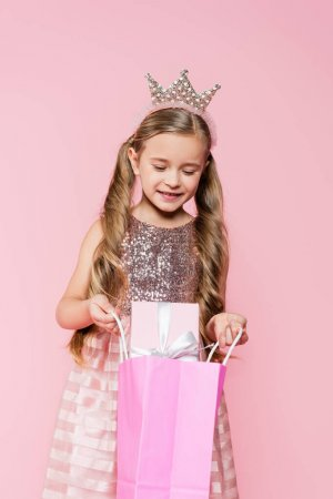 Photo for Little girl in dress and crown holding shopping bag with present isolated on pink - Royalty Free Image