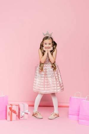 Photo for Full length of excited little girl in crown standing near presents and shopping bags on pink - Royalty Free Image