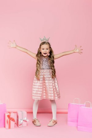 Photo for Full length of excited little girl in crown standing with outstretched hands near presents and shopping bags on pink - Royalty Free Image