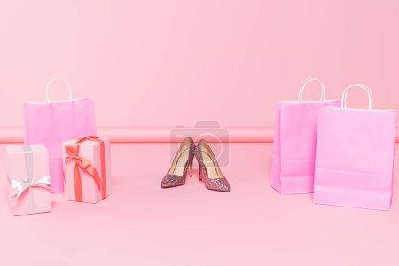 talons près de sacs à provisions et coffrets cadeaux sur rose