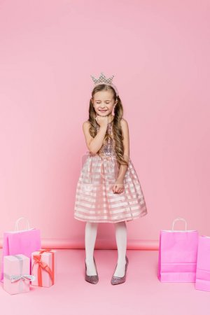 Photo for Full length of happy little girl in crown standing on heels near presents and shopping bags on pink - Royalty Free Image