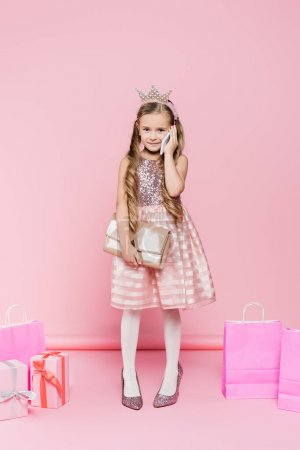 Photo for Full length of happy little girl in crown standing on heels and talking on smartphone near presents and shopping bags on pink - Royalty Free Image