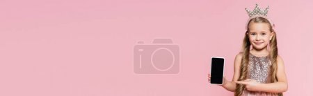 Photo for Happy little girl in crown pointing with finger at smartphone with blank screen isolated on pink, banner - Royalty Free Image