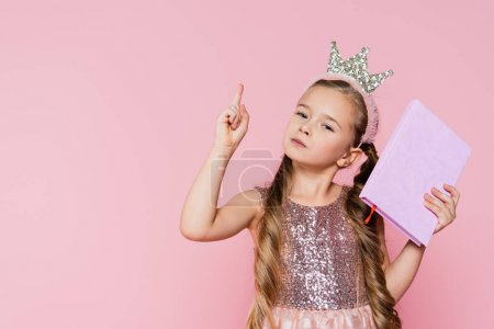 Photo for Little girl in crown holding book and pointing with finger isolated on pink - Royalty Free Image