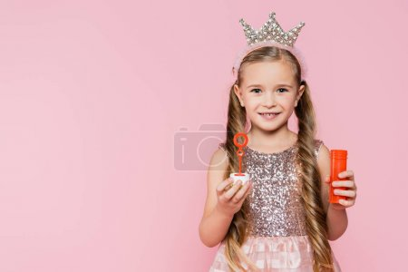 Photo for Happy little girl in crown holding soap bubbles isolated on pink - Royalty Free Image