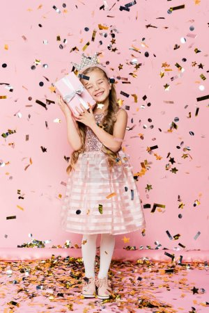 Photo for Full length of happy little girl in crown holding present near falling confetti on pink - Royalty Free Image