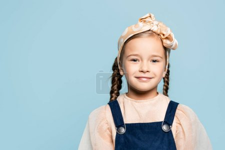 Photo for Cheerful kid in headband with bow looking at camera isolated on blue - Royalty Free Image