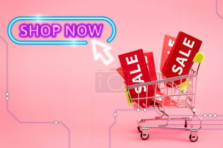 red labels with sale in small shopping trolley near shop now lettering on pink