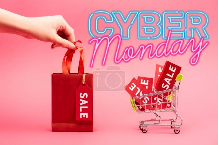 cropped view of woman holding small shopping bag near cart with sale tags near cyber monday lettering on pink