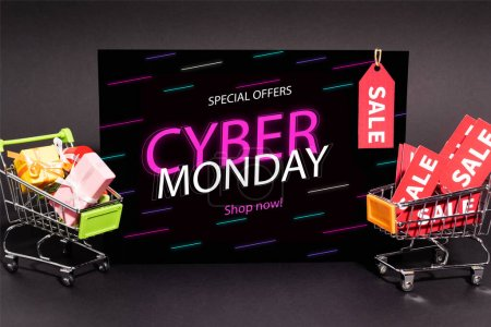 small presents in toy shopping carts near placard with special offers, cyber monday, shop now lettering on dark background