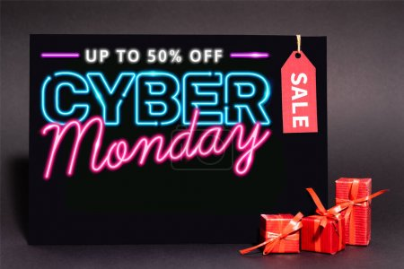 Photo for Placard with up to 50 percent off, cyber monday lettering and sale tag near presents on dark background - Royalty Free Image