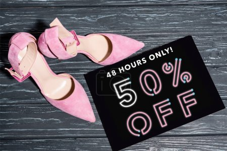 top view of pink shoes near placard with 48 hours only, 50 percent off lettering on wooden surface