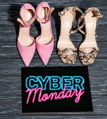 top view of trendy shoes near board with cyber monday lettering on wooden surface
