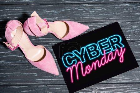 Photo pour Vue du dessus des chaussures roses près de la plaque avec lettrage cyber lundi au néon sur la surface en bois - image libre de droit