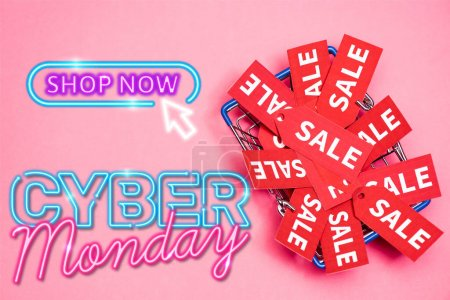 top view of sale tags in shopping basket near shop now, cyber monday lettering on pink, black friday concept