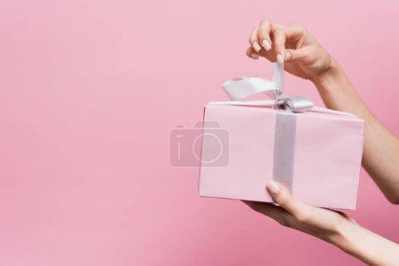 Photo pour Vue partielle de la femme tenant un ruban sur présent enveloppé isolé sur rose - image libre de droit