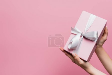 partial view of woman holding wrapped present isolated on pink