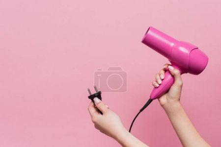 cropped view of woman holding cable with plug and hair dryer isolated on pink