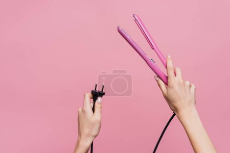 cropped view of woman holding hair straightener in hands isolated on pink