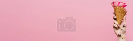 Photo for Partial view of woman holding waffle cone with petals in hand with flowers covered by plasters isolated on pink, banner - Royalty Free Image