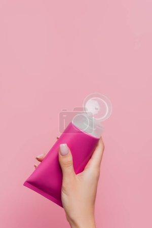 Photo pour Vue partielle de la femme tenant tube avec lotion à la main isolé sur rose - image libre de droit