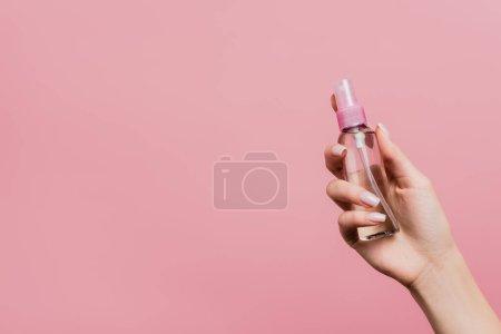 Photo pour Vue recadrée de la femme tenant pulvérisation de parfum à la main isolé sur rose - image libre de droit