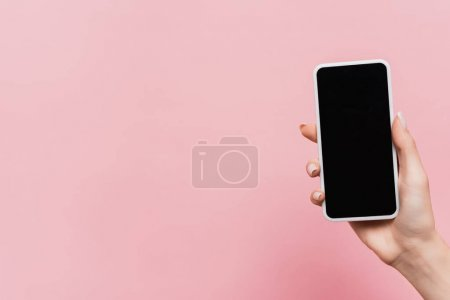 cropped view of woman holding smartphone with blank screen in hand isolated on pink