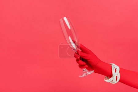 Photo for Cropped view of woman in glove holding empty champagne glass isolated on red - Royalty Free Image