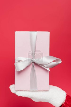 Photo for Cropped view of woman in white glove holding pink present isolated on red - Royalty Free Image