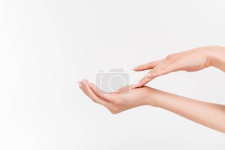Photo pour Vue partielle de la femme sur la main touchante de la femme tout en appliquant la crème pour les mains isolée sur blanc - image libre de droit