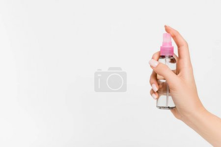 cropped view of woman holding spray bottle with aromatic liquid in hand isolated on white