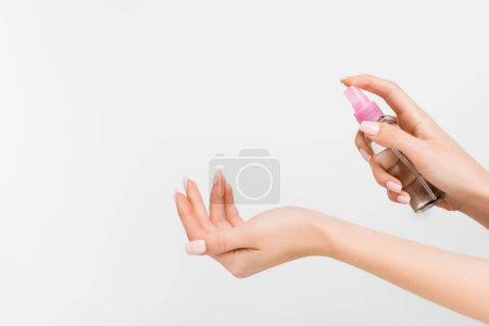 Photo pour Vue recadrée de la femme tenant le flacon pulvérisateur avec du liquide isolé sur blanc - image libre de droit