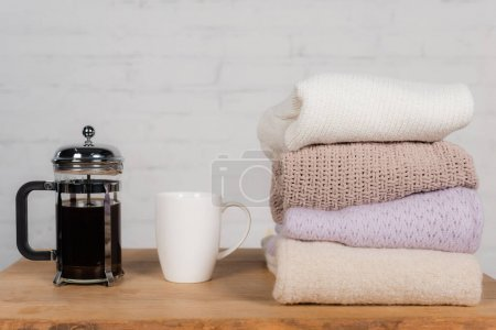 Cup and teapot near knitted sweaters on table on brick wall background