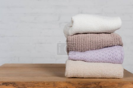 Photo for Warm and knitted sweaters on wooden table on white background - Royalty Free Image