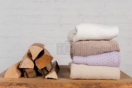 Photo pour Grumes en bois près de chandails tricotés chauds sur table sur fond blanc - image libre de droit