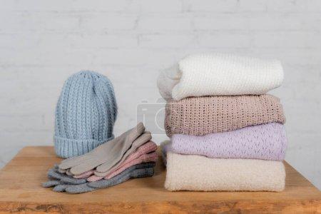 Photo pour Chapeau, chandails et gants en laine sur table en bois sur fond blanc - image libre de droit