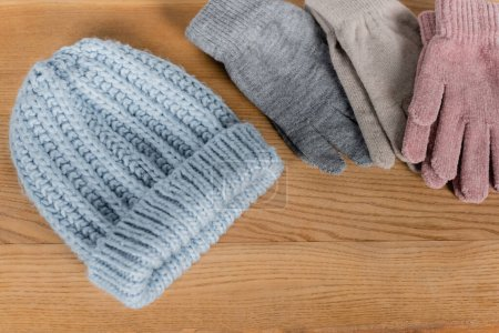 Top view of knitted hat and gloves on wooden surface