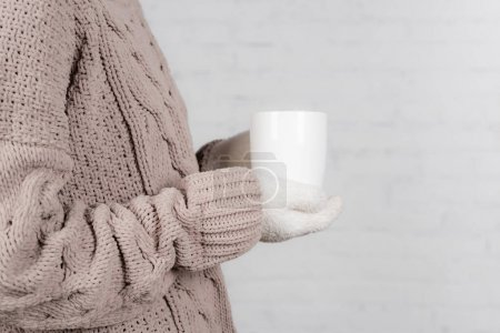 Cropped view of woman in warm sweater and gloves holding cup on white background