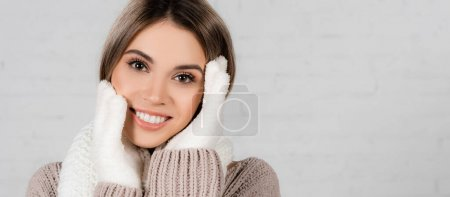 Smiling woman in knitted sweater and soft gloves looking at camera on white background, banner