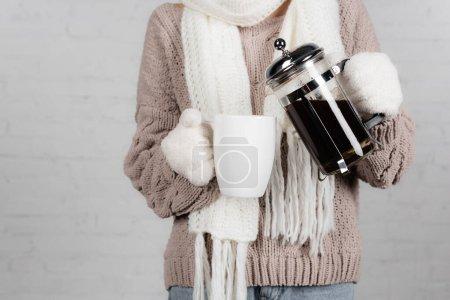 Photo pour Vue recadrée de la femme en pull tricoté, écharpe et gants chauds versant du café à partir du pot dans une tasse sur fond blanc - image libre de droit