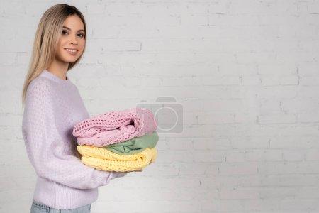 Jeune femme avec des pulls tricotés colorés regardant la caméra sur fond blanc