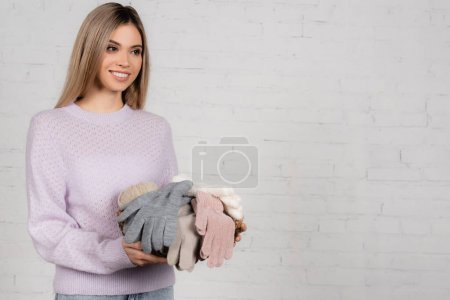 Smiling woman in warm sweater holding basket with gloves and yarn on white background