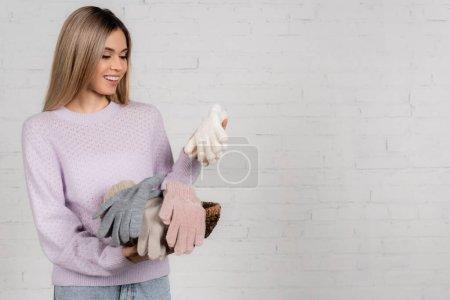 Photo pour Femme gaie regardant des gants chauds tout en tenant le panier avec du fil sur fond blanc - image libre de droit